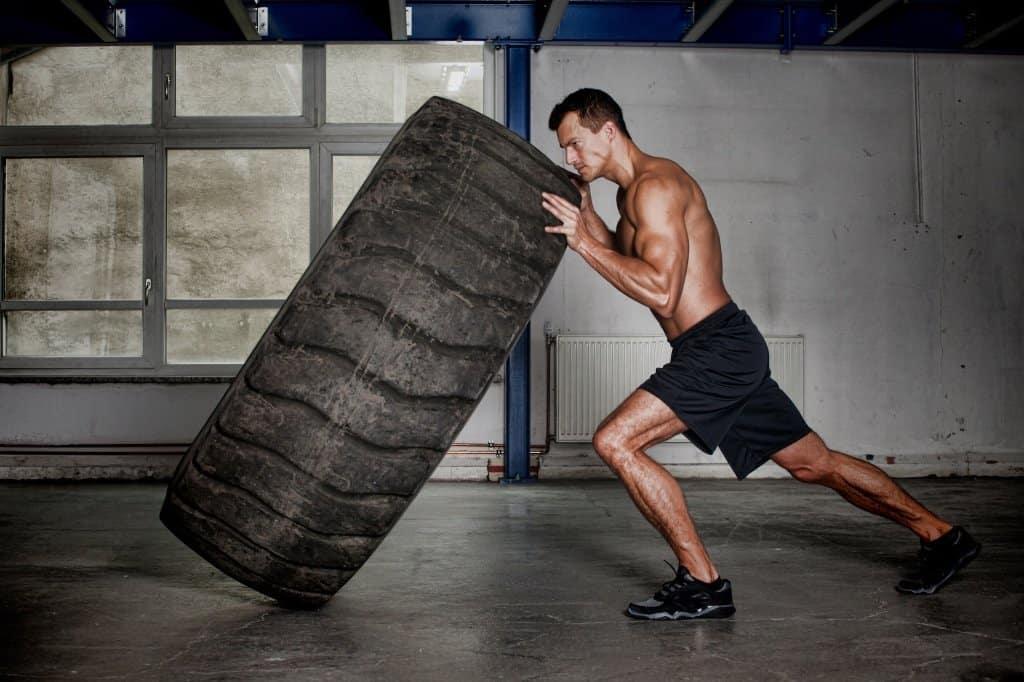 man presses a large tire