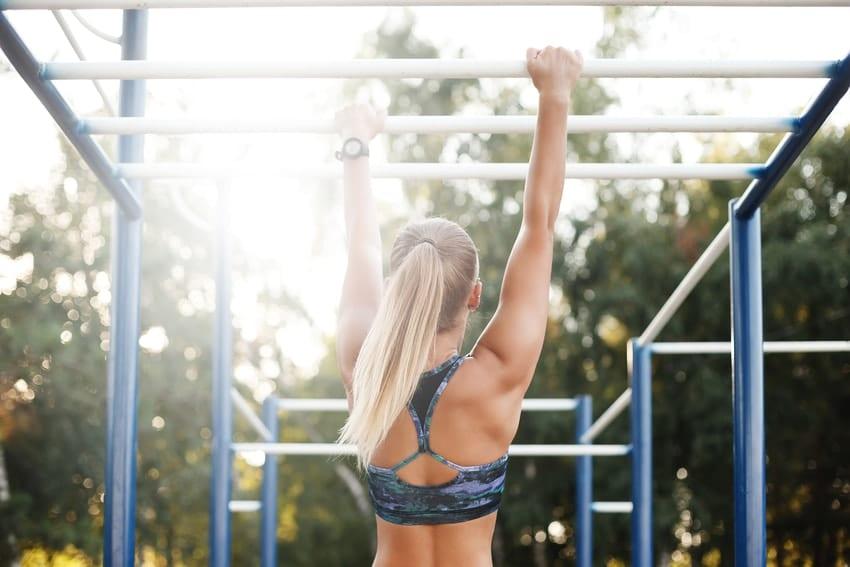 woman training outside on monkey bars